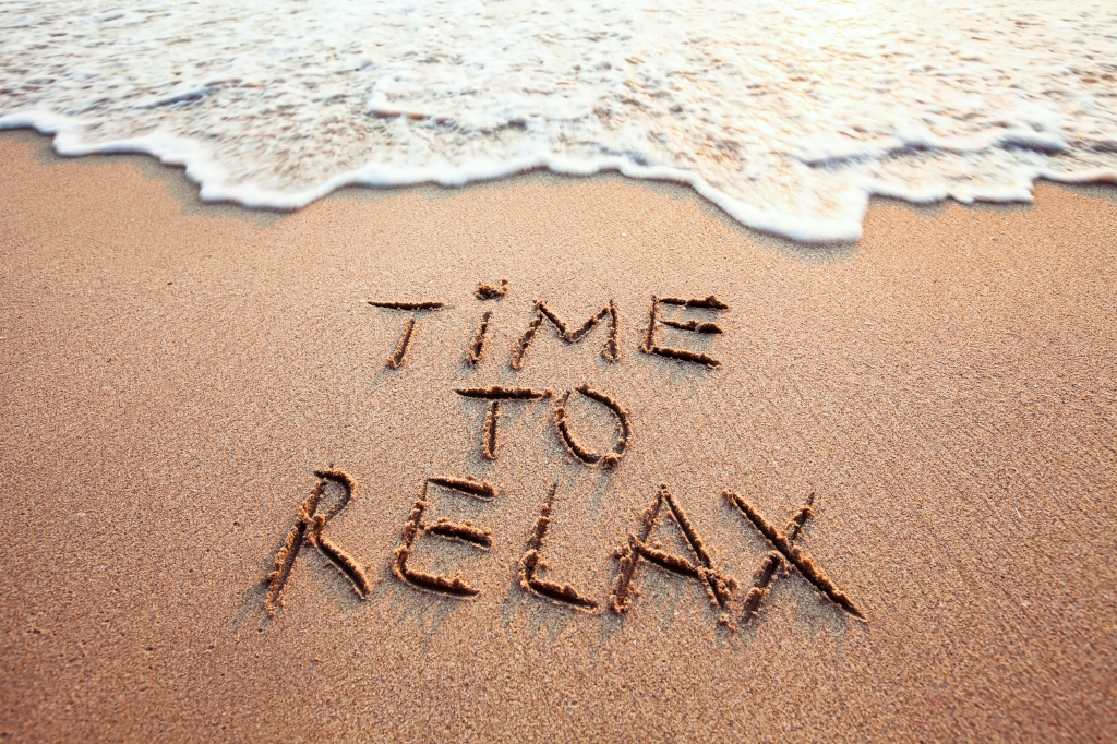 "Picture of a beach with ""Time to relax"" written in the sand as the surf comes in."